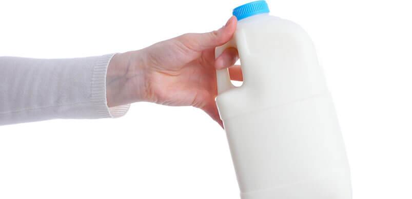 Hand Holding Plastic Milk Bottle