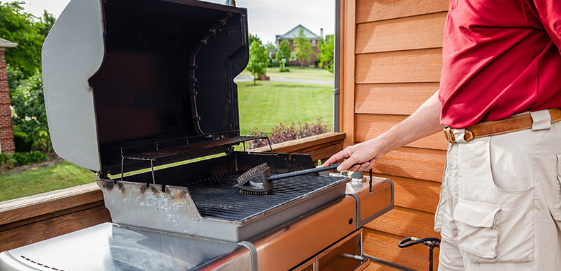 Man Cleaning Grill With Wire Brush