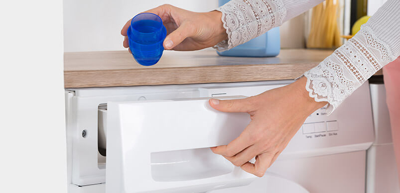 Hands Pouring Detergent In The Washing Machine