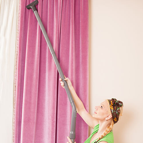 Woman Hoovering Top Of Curtains