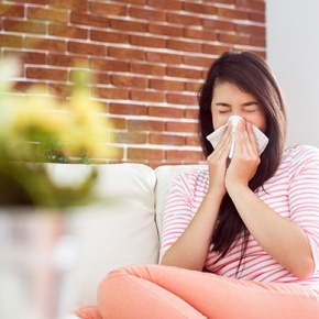 Woman At Home Blowing Her Nose