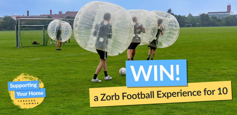 People Playing Zorb Football With Win Sign