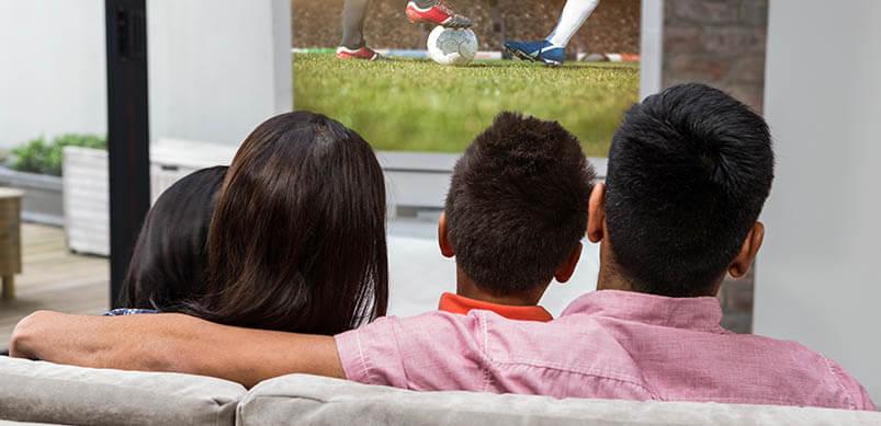 Family On Sofa Watching TV
