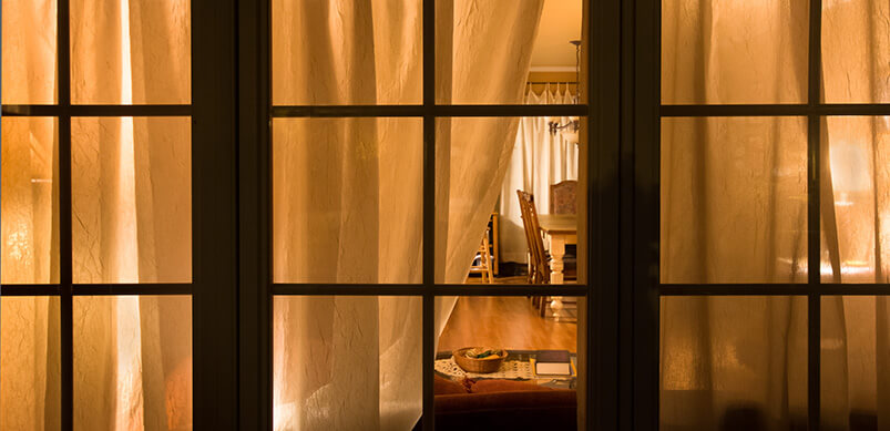 Open Curtain Showing Living Room With Light On
