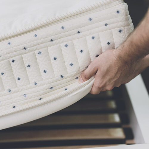 Close Up Of Hand Lifting Mattress