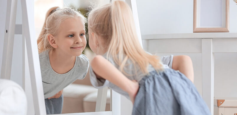 Girl Looking at Herself In Stand Up Mirror