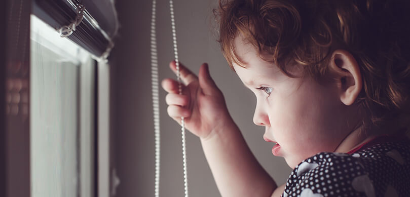 Child Looking Out Window Holding Blind Cord