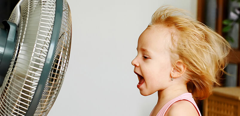 Girl Sitting In Front Of Fan With Hair Blowing