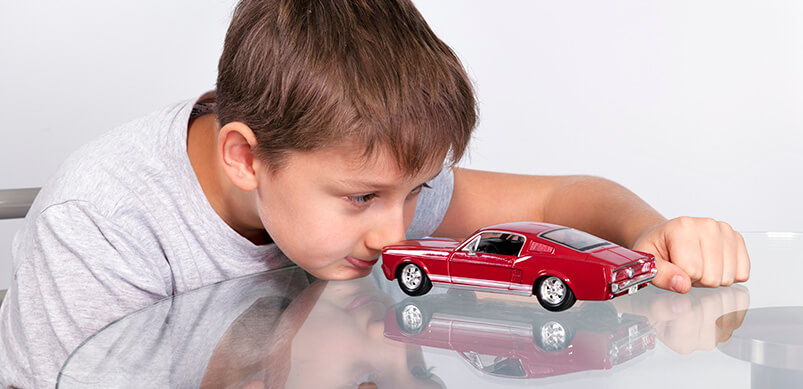 Boy Playing With Toy Car On Glass Table
