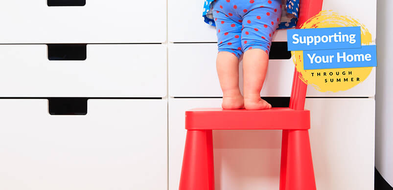Child Standing On Chair By Chest of Drawers