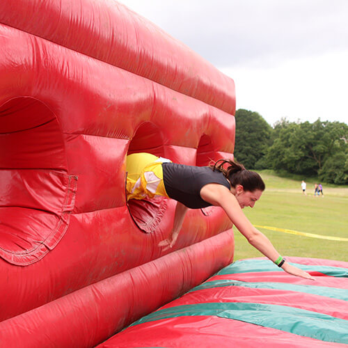 Emma From Team Climbing Through Obstacle