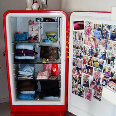 Open Broken Fridge With Folded Clothes And Photos On Door