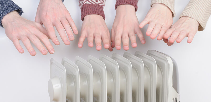 Hands Hovering Over Heater