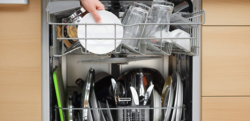Very Full Dishwasher With Plates In The Cup Compartment