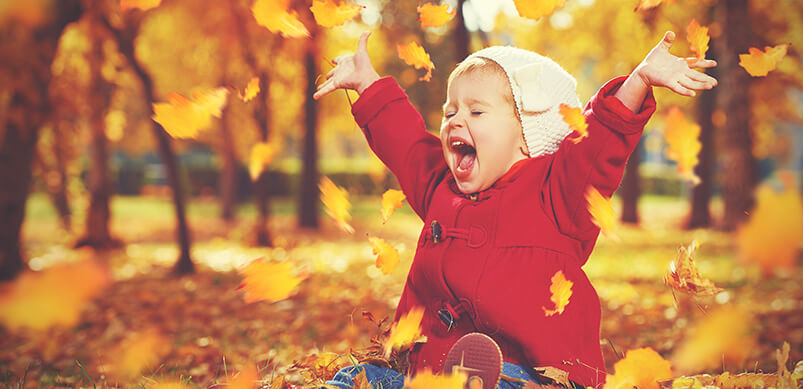 Young Girl In Coat Playing In Leaves