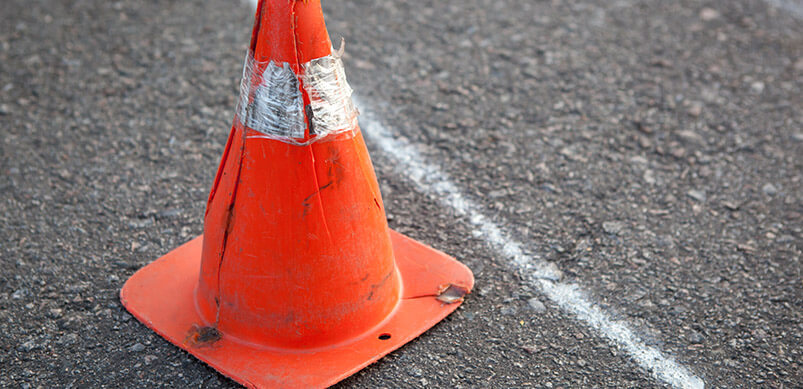 Cracks On Road With Hazard Cone