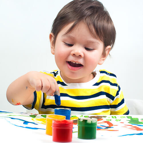 Child Using Coloured Paints On Paper