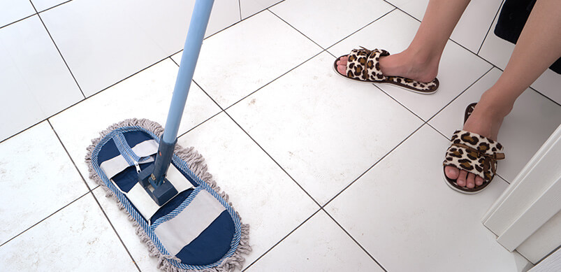 Person Cleaning Tiled Floor With Mop