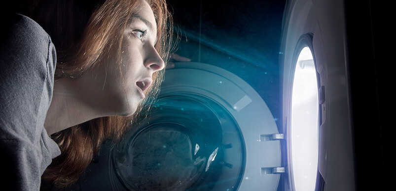 Woman Looking Into Light Inside Washing Machine. Magical