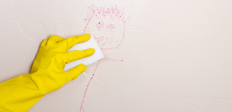 Gloved Hand Cleaning Crayon Off Wall