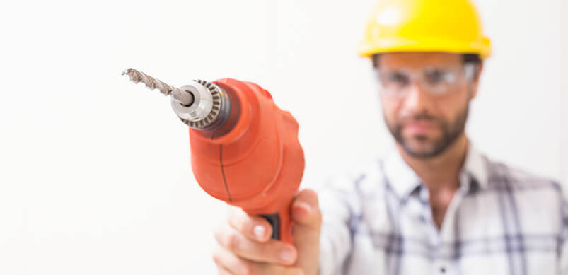 Man With Hard Hat and Glasses Pointing Power Drill