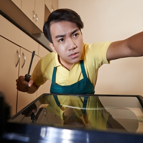 View Of Man Fixing Oven From Inside
