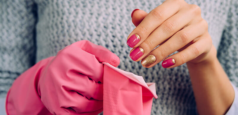 Lady With Painted Nails Putting On Rubber Gloves