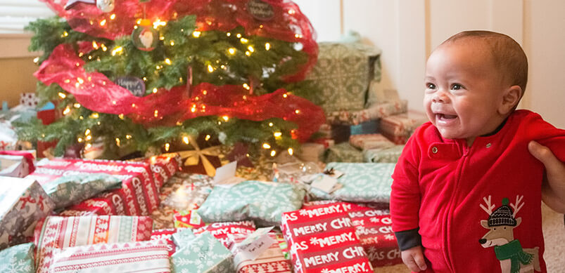 Baby Next To Christmas Presents