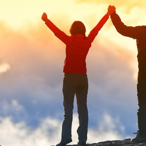 Couple Standing On Top Of Mountain