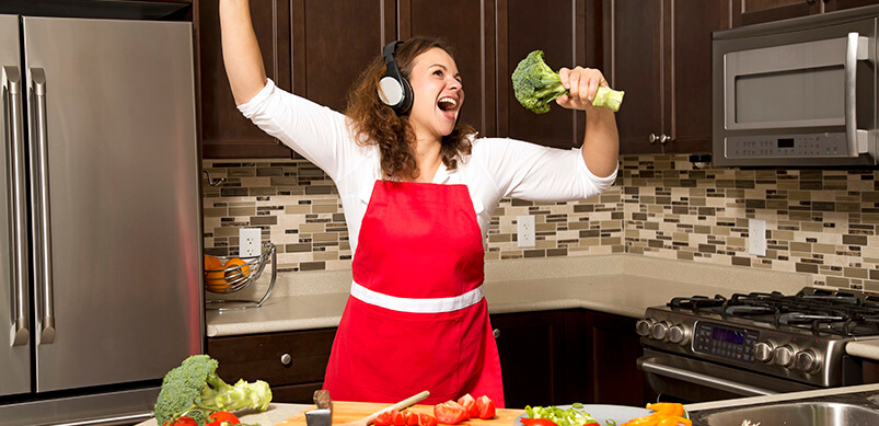Woman Singing Into Broccoli In Kitchen