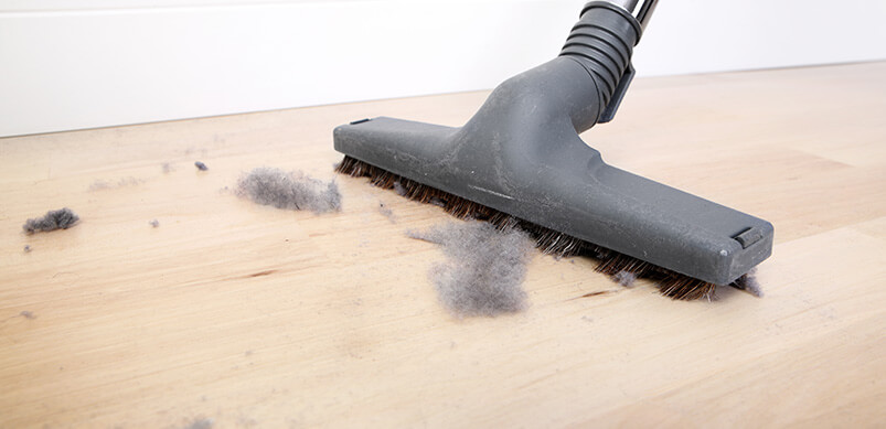 Vacuum Cleaning Wooden Floor Covered With Dust