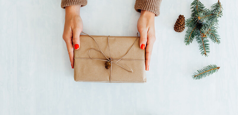 Hands Holding Present Wrapped In Brown Paper