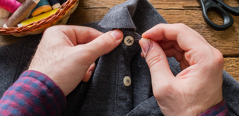 Man Sewing Button Onto Shirt