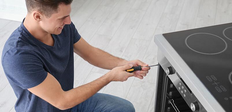 Man Repairing Oven In Kitchen