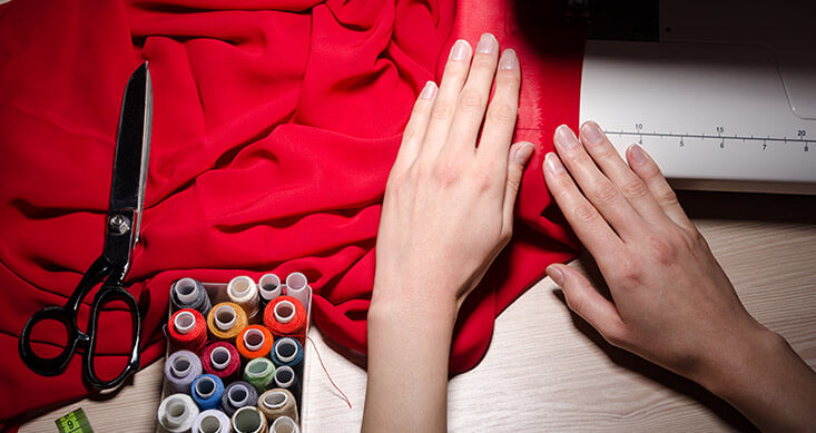 Hands Fixing Clothes With Sewing Machine