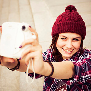 Woman Taking A Selfie With Polaroid Camera