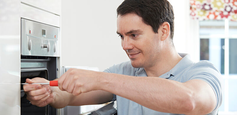 Man Fixing Oven In Kitchen
