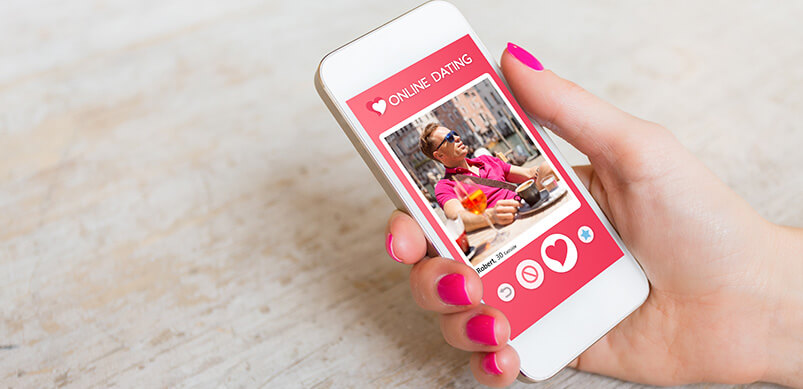 Woman's Hand Using Online Dating App On Phone