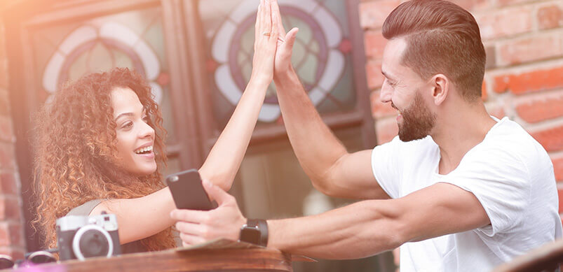 Man And Women High Fiving At Dinner