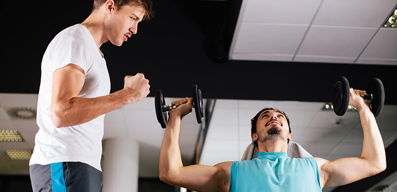 Two Men In The Gym Motivating Each Other