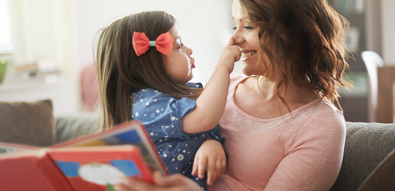 Woman Reading Story To Young Girl