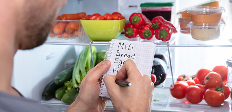 Close Up Of Man Writing Shopping List By Open Fridge