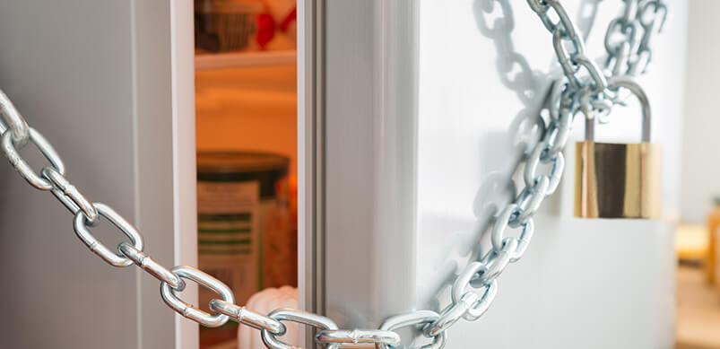 Padlock And Chain Around Open Fridge