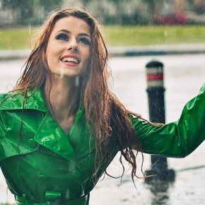 Woman Standing In Pouring Rain With Arms Up