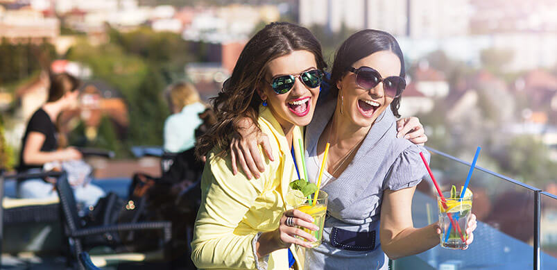 Girls Smiling And Drinking At Rooftop Bar