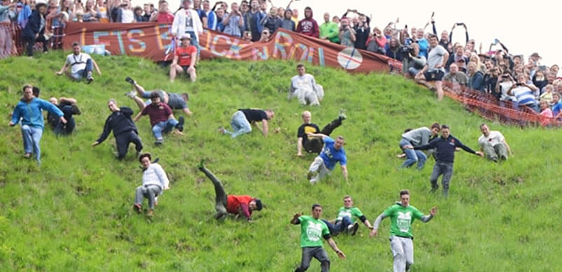 People Taking Part In Cheese Rolling