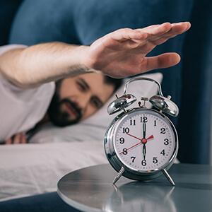 Man Turning Off Alarm In Morning
