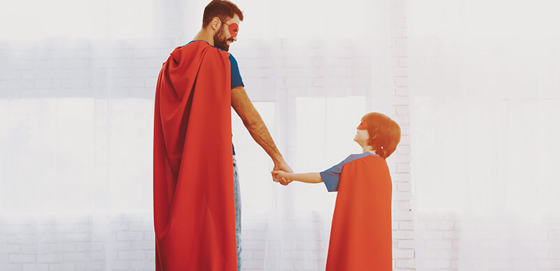 Father And Son In Superhero Capes Holding Hands