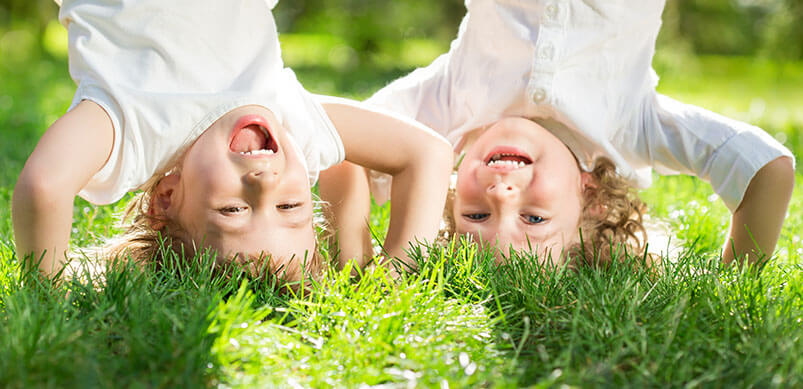 Children Doing Hand Stands On Grass