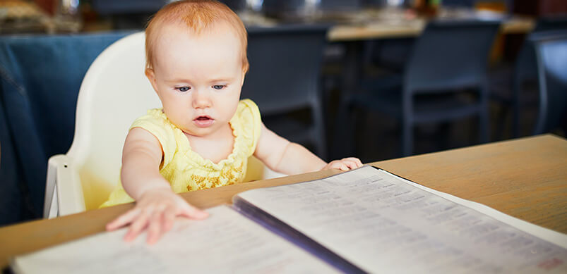Toddler Reading Menu In Restaurant